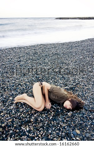Beautiful woman laying on the beach with sad gesture. Long exposed waves. - stock photo