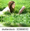 beautiful woman lays on green field and reads book - stock photo