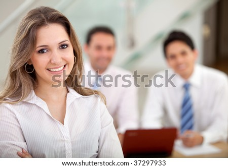 Beautiful woman leading a busines group in an office - stock photo