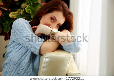 Beautiful woman leaning on the sofa at home - stock photo
