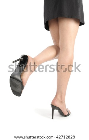 Beautiful woman  legs and feet with black dress over white background