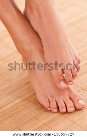 Beautiful woman legs in a spa on bamboo cover