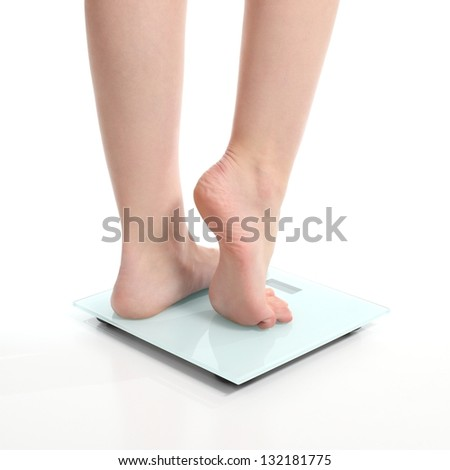 Beautiful woman legs on a scale on a white isolated background