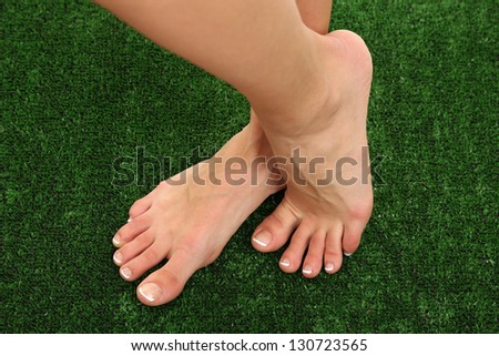 Beautiful woman legs on green grass - stock photo
