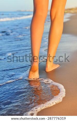 Beautiful woman legs, walking on the beach - stock photo