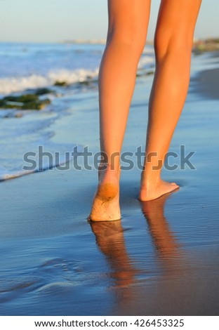 Beautiful woman legs, walking on the beach - stock photo