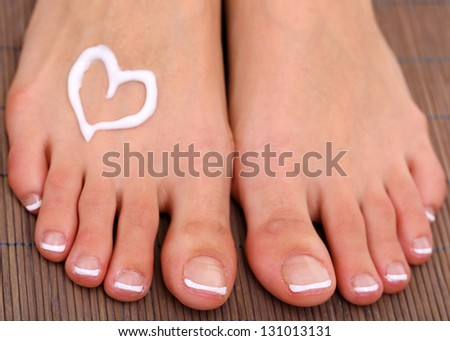 Beautiful woman legs with cream on bamboo mat - stock photo