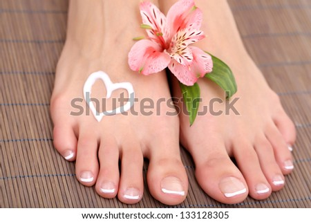 Beautiful woman legs with cream on bamboo mat - stock photo