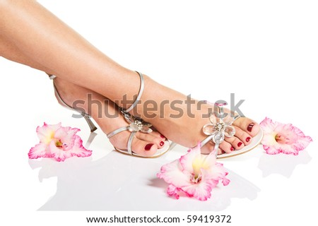 Beautiful woman legs with red manicure on feet and flowers - stock photo