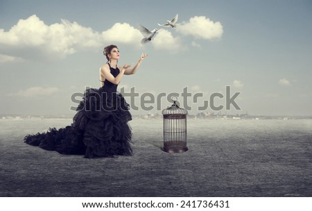Beautiful woman lets the birds out of the cage outdoors. - stock photo