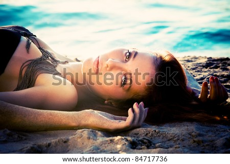 beautiful woman lie in sand by the river, sunset - stock photo