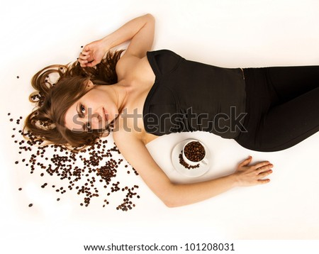 Beautiful woman lie on coffee beans on white background. She is looking at camera. - stock photo