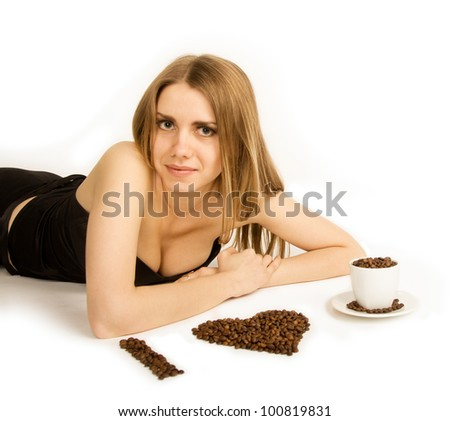 Beautiful woman lie on white background with coffee beans and cup. She is looking at camera. - stock photo