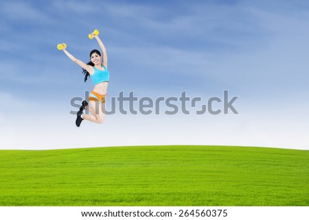 Beautiful woman lifting dumbbell and jumping on the meadow - stock photo