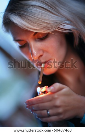 Beautiful woman lighting cigarette. Close-up, shallow DOF. - stock photo
