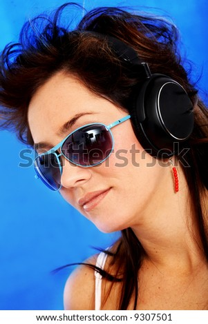beautiful woman listening and wearing sunglasses over a blue background