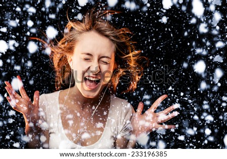 Beautiful Woman Listening Music and screams on a snowfall background