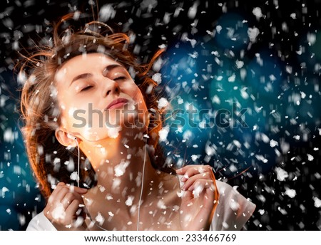 Beautiful woman listening to music during a snowfall - stock photo