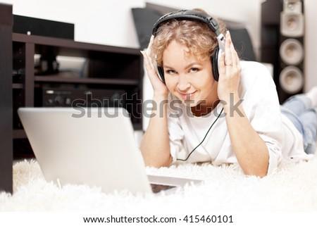 Beautiful woman listening to music lying on the floor - stock photo