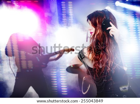 Beautiful woman listening to music with headphones. Live music background with guitar and bright lights on stage. Live music and party concept.