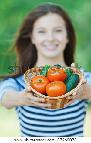 beautiful woman long hair blurred offers basket vegetables - stock photo