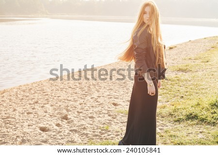 beautiful woman long red hair on a wind near the lake develop - stock photo