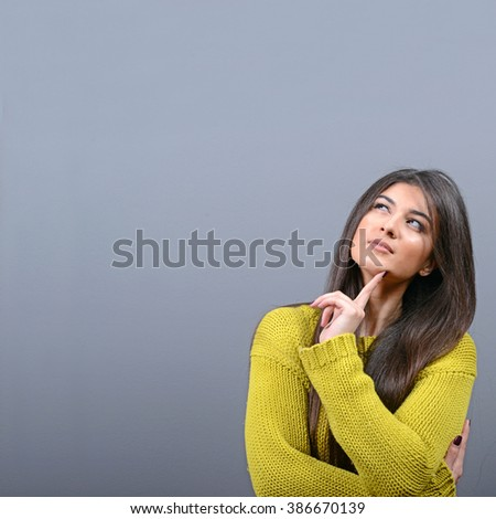 Beautiful woman looking at blank area against  gray background - stock photo