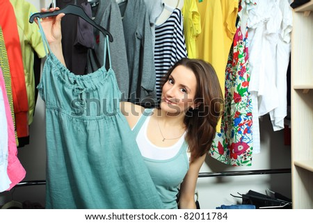 Beautiful woman looking at her clothes in a wardrobe at home.
