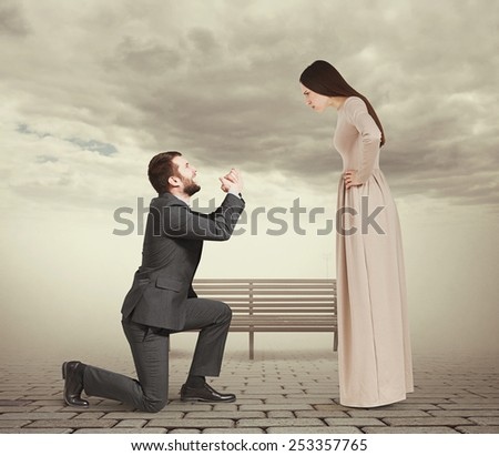 beautiful woman looking at man standing on knee and apologizing. photo in foggy park - stock photo