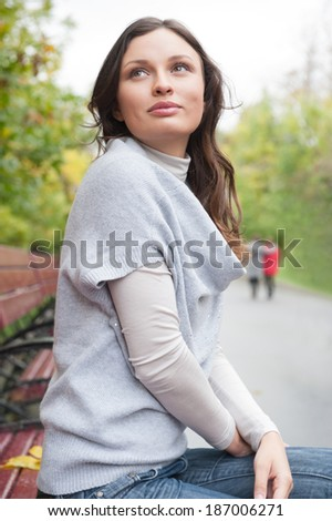 Beautiful woman looking at something while sitting on the bench at park - stock photo