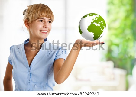 Beautiful woman looking at the earth in her hand - stock photo