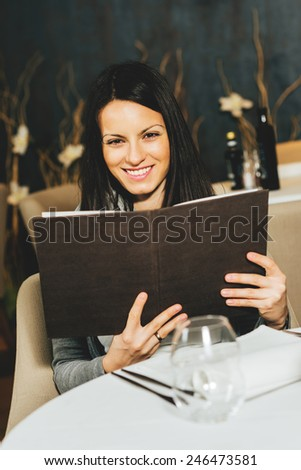 Beautiful woman looking at the menu in a restaurant - stock photo
