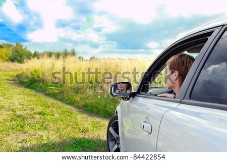Beautiful woman looking from window of sport car in the field under bright blue sky - stock photo