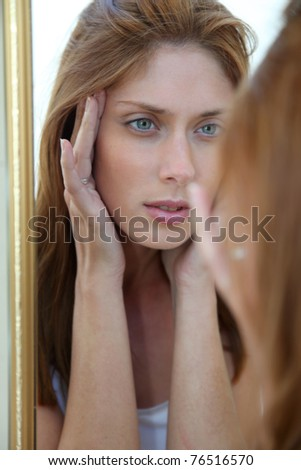 Beautiful woman looking in a mirror