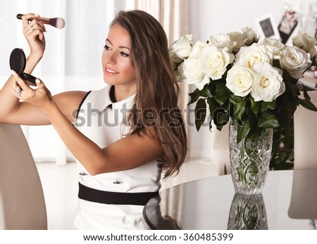 Beautiful woman looking in the mirror and applying cosmetic with a big brush. Holidays, makeup, people and celebration concept - stock photo
