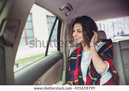 Beautiful woman looking in the window sitting in moving car
