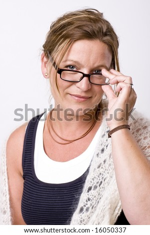Beautiful woman looking into camera with a friendly smile. She has a pencil in her hand. - stock photo