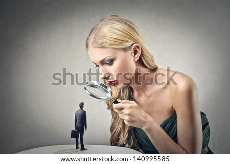 beautiful woman looking little man with magnifying glass - stock photo