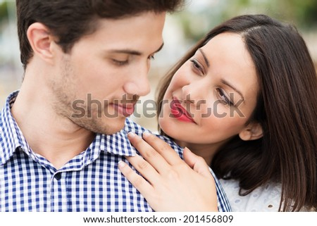 Beautiful woman looking lovingly at her husband as she leans on his shoulder from behind looking into his face - stock photo