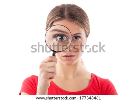 Beautiful woman looking through a magnifying glass, isolated on white
