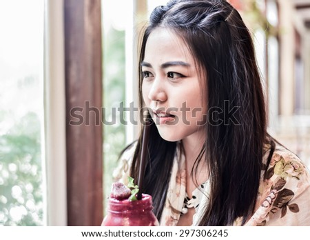 Beautiful woman looking through a window. - stock photo