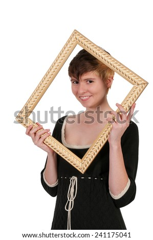 Beautiful woman looking through an ornate picture frame - stock photo