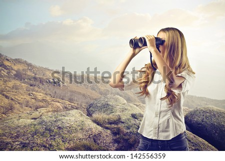 beautiful woman looking through binoculars - stock photo