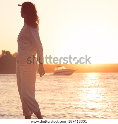 Beautiful woman looking to the golden sunshine glow of sunset with arm near face enjoying peace, serenity in nature. Retro style photo - stock photo