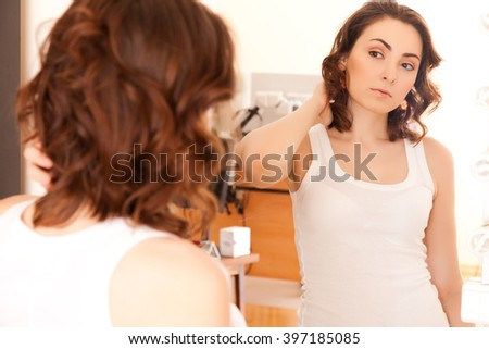 Beautiful woman looking to the mirror at studio - stock photo