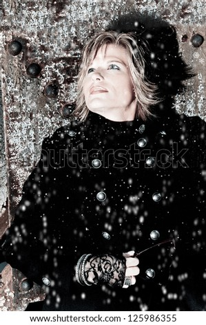 Beautiful Woman looking up at the snow - stock photo