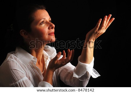 Beautiful woman looking up to heavenly light in attitude of devotion and serenity - stock photo