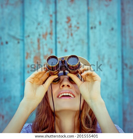 Beautiful woman looking up with binoculars. focus on mouth, copy space above - stock photo