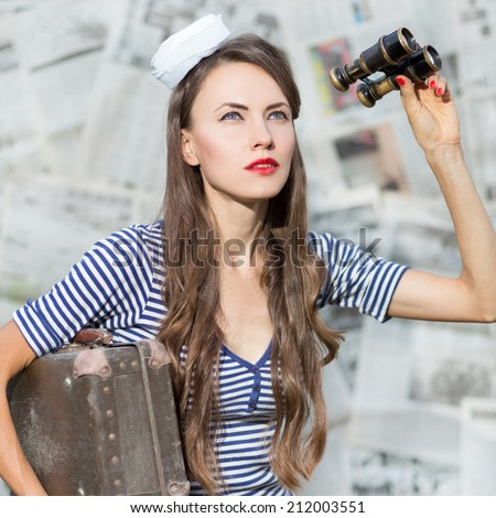 Beautiful woman looking up with binoculars. Sailor girl in marine stripes dress over grey newspaper background - stock photo