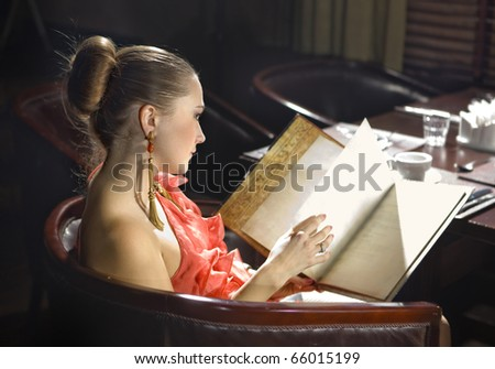 beautiful woman looks on menu at expensive restaurant